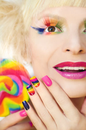 artificial nails: Rainbow manicure on artificial nails square shape, with a Lollipop in hand and colorful makeup.