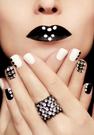 Multicolored manicure with white and black nail Polish decorated with rhinestones and a ring on his hand. Archivio Fotografico