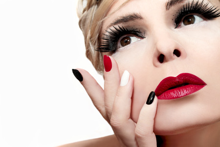 Make-up met rode lippen, borstelige wenkbrauwen, valse wimpers en gekleurde nagels.