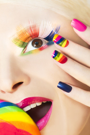 red nail colour: Rainbow manicure on artificial nails square shape, with a Lollipop in hand and colorful makeup.