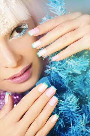 christmas manicure: Pastel Christmas French manicure and makeup with a garland. Stock Photo