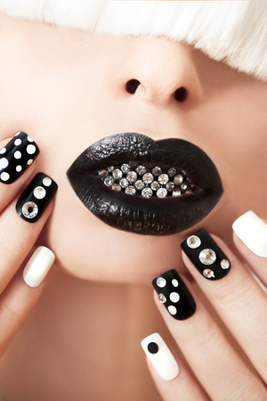 black makeup: Makeup and manicure with rhinestones and white with black nail Polish.
