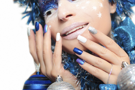 christmas manicure: Blue festive manicure with colorful nail Polish and silver Christmas ball in the hand. Stock Photo