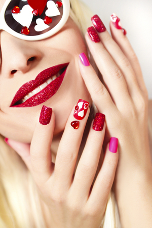 Manicure and makeup with red sequins and hearts of different shapes and colors on the girl with glasses with long white hair.