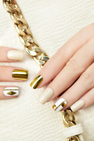 Gold manicure with rhinestones, chain and a reptile texture.