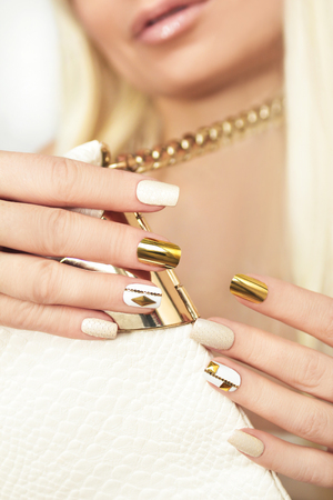rhinestones: Gold manicure with rhinestones, chain and a reptile texture.