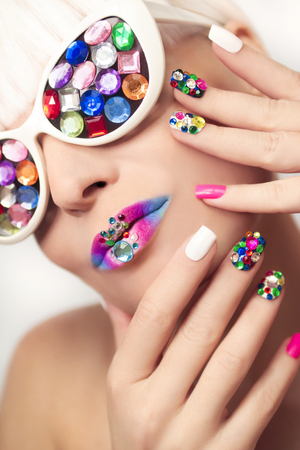 Makeup and manicure with multicolored crystals and glasses on the blonde girl. Banque d'images
