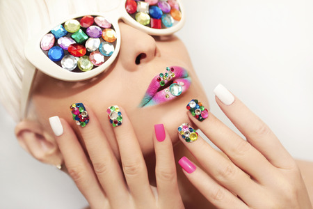acrylic nails: Makeup and manicure with multicolored crystals and glasses on the blonde girl. Stock Photo