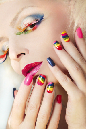 Rainbow manicure on artificial nails square shape on the girl and colorful makeup.