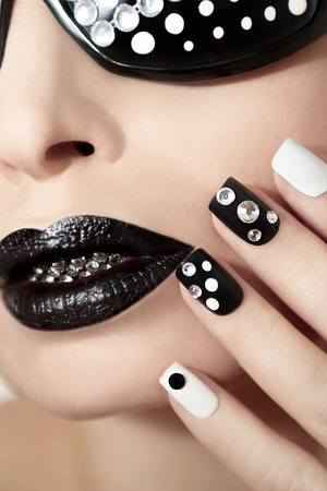 woman body: Black and white makeup and manicure with rhinestones and glasses.