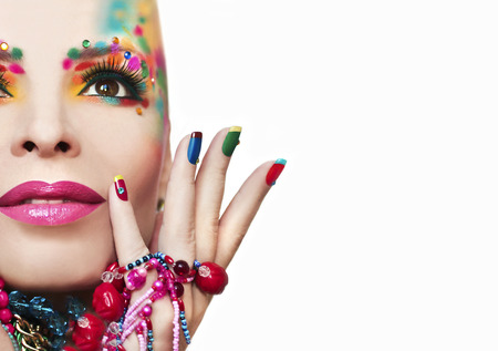 Colorful French manicure and makeup on a girl with rhinestones and decorations on a white background.