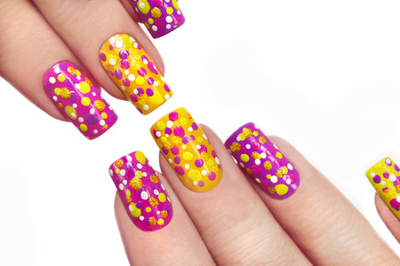 Multicolored manicure with dots of different shapes and colors on a white background.