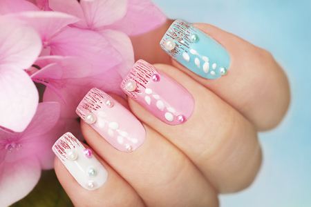 Colored manicure with rhinestones and pearl sequins with pink hydrangea in a woman's hand.