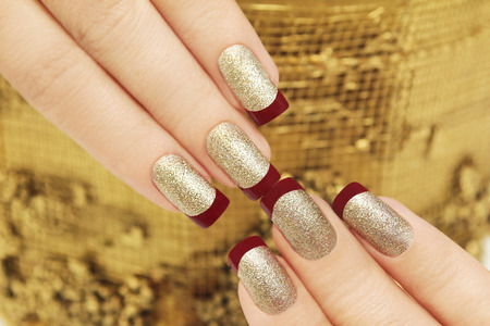 french manicure: Golden maroon French manicure on womans hands are rectangular. Stock Photo
