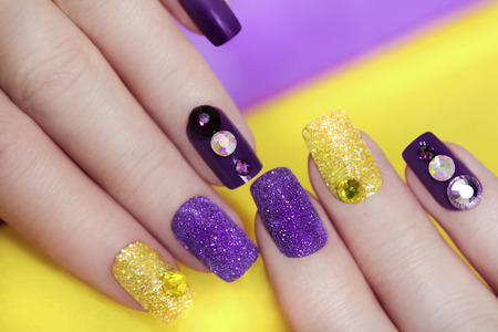 artificial nails: Lilac purple manicure with gold glitter and rhinestones in different colors on a purple background.