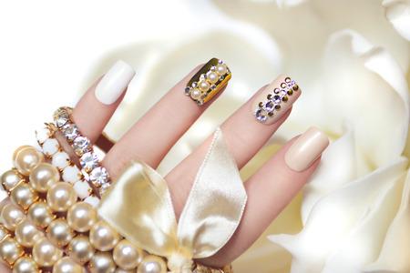 Pearl manicure met steentjes op een gouden achtergrond en pastel nagels op vrouwelijke hand met decoratie.