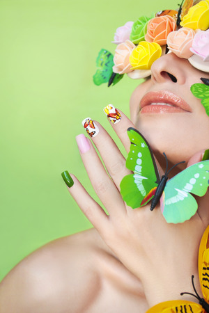 health woman: Multicolored manicure with pictures of butterflies on the nails and decorative rosettes on the eyes of a young woman.