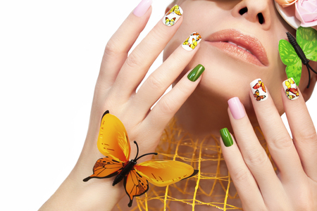 animal body part: Multicolored manicure with pictures of butterflies on the nails and decorative rosettes on the eyes of a young woman.