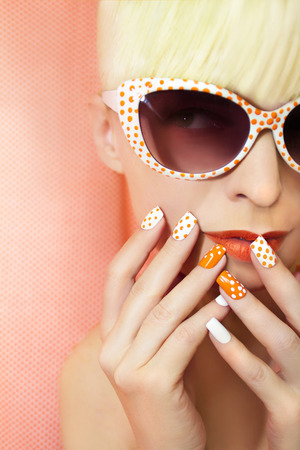acrylic nails: Sunny orange manicure with dots on the womens nails and makeup closeup in sunglasses.