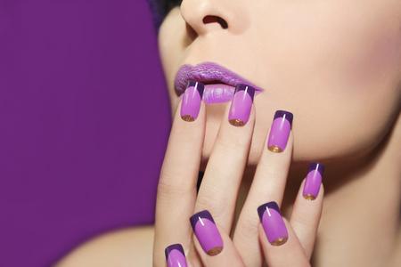 visage profil: lèvre Mauve et manucure française avec des paillettes d'or sur un fond violet. Banque d'images