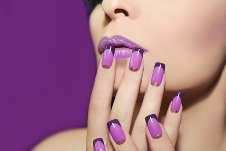 profile face: Mauve lip and French manicure with gold glitter on a purple background.