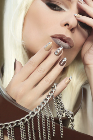 pastes: Makeup and manicure in brown and beige shades with a pattern of chains and rhinestones on very oval nails.