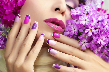 The French pink lilac manicure and makeup with phloxes on the girl. Archivio Fotografico
