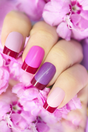 Maroon pink multicolored French manicure with flowers in hand.