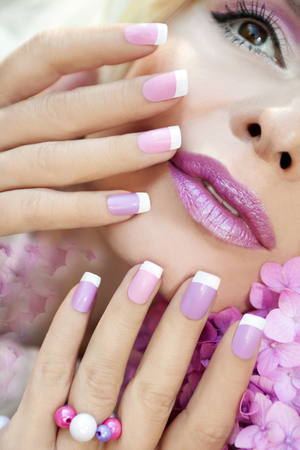 french model: Pink purple French manicure and makeup on the girl with the hydrangea closeup.