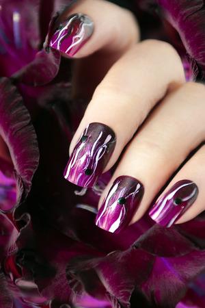 Manicura púrpura con líneas onduladas blancas y rhinestones negro en una mano femenina.