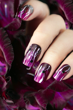 Purple manicure with white wavy lines and black rhinestones on a female hand.