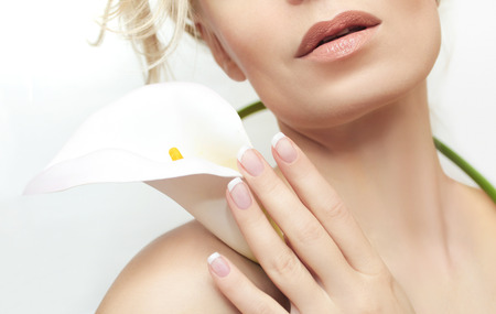 The classic French manicure on female hand with a white flower.