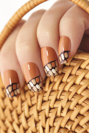 Straw twisted manicure on female hand beige yellow closeup.
