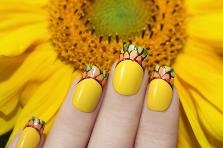 finger shape: Yellow French manicure with a design on female hand with sunflower closeup. Stock Photo