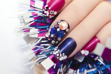 christmas manicure: Christmas winter blue manicure with rhinestones of different shapes and sparkles of snow on female hand with a garland. Stock Photo