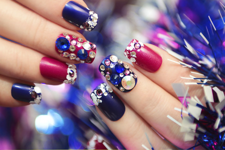 christmas manicure: Christmas winter blue manicure with rhinestones of different shapes and sequins in the form of snow on female hand with tinsel.