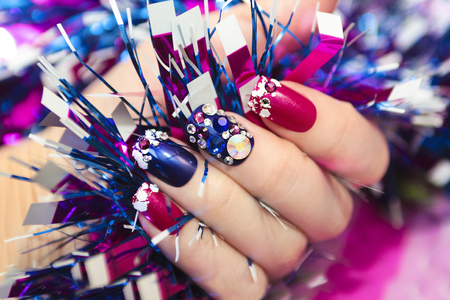 sequins: Christmas winter blue manicure with rhinestones of different shapes and sequins in the form of snow on female hand with tinsel.