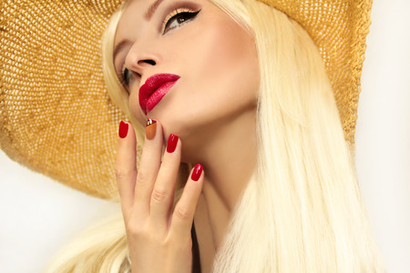 Red straw nail design girl model with red lips and a straw hat on his head. Stock Photo