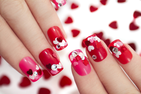 Nail designs with different sequins in the shape of hearts on red and pink nails for girls. Stock Photo