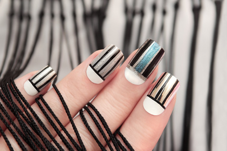 Gray striped nail design on female hand close up.