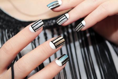rayas de colores: Gris diseño de uñas de rayas en la mano femenina de cerca.