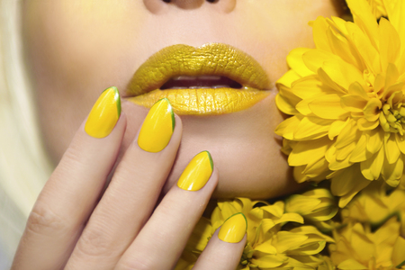Yellow makeup and manicure with a sharp oval shape of the nails on the woman with the flowers closeup.