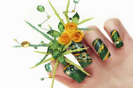 Nageldesign mit Acryl gelbe Rosen und Blätter Hand-weibliche Hand mit Pailletten, Strasssteine, Perlen auf einem weißen Hintergrund closeup.