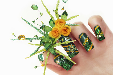 Nail design with acrylic yellow roses and leaves hand-female hand with sequins, rhinestones, beads on a white background closeup.