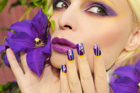 clematis: Summer purple yellow makeup and manicure with design on long square nails on the woman with the flower Clematis.