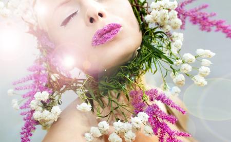 灰色の背景に白とピンクの花に囲まれた喜びの感覚を持つ美しい少女。ライブ花の要素を持つピンクの唇。