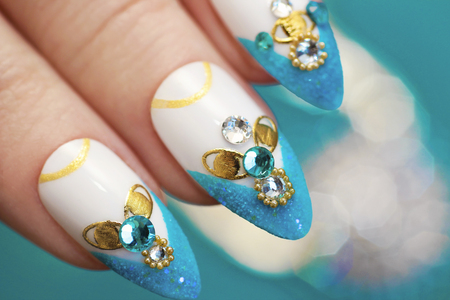 Luxurious glamorous sandy blue French manicure with rhinestones, boulongne and gold plated womens nails closeup. Stock Photo