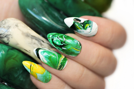 sharply: Stone nail design in white and green colors with veins of dark and yellow color nail Polish on a sharply oval-shaped nails closeup. Stock Photo