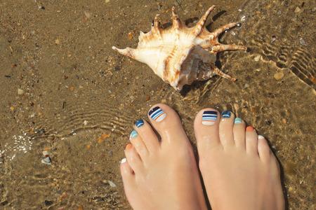 Marine striped multicolored pedicure on female nails on summer sea closeup. 版權商用圖片