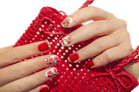 白の背景にバラのデザインと赤フランスのマニキュアとペディキュア。